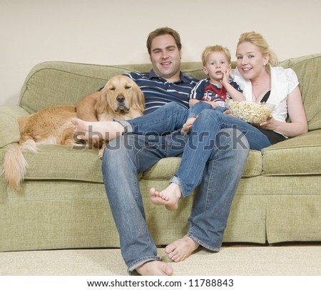 young family sitting on sofa and eating popcorn