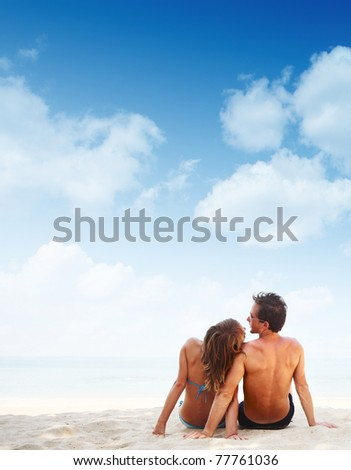 Young family sitting on warm sand by a sea with blue sky background