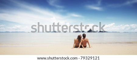 Young family sitting on white sand by sea and looking to the horizon