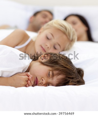 Young family sleeping together in parent's bed