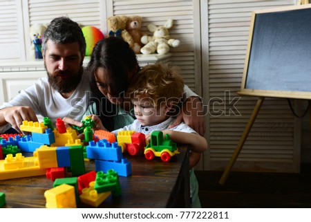 Young family spends time in playroom. Mom, dad and kid with toys on room background build out of plastic blocks. Family and childhood concept. Parents and son with busy faces make brick constructions #777222811