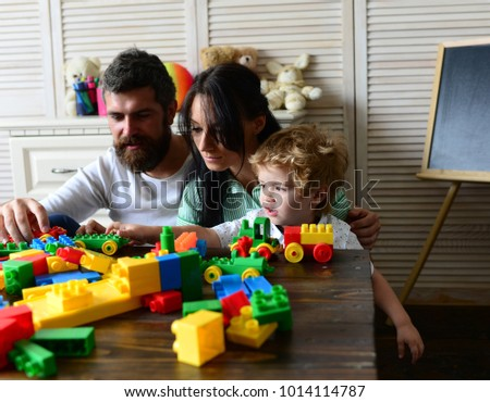 Young family spends time in playroom. Parents and son with busy faces make brick constructions. Love and family games concept. Mom, dad and kid with toys on room background build out of plastic blocks #1014114787