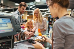 Young family standing at the cash counter buying groceries at the supermarket