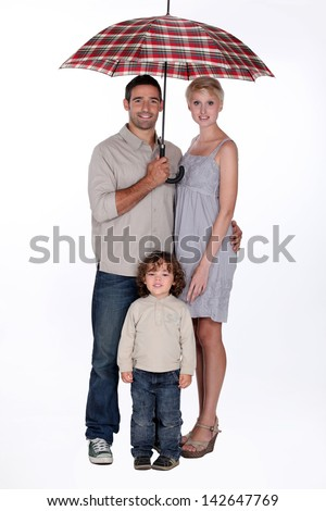Young family standing underneath an open umbrella