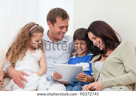 Young family using tablet on the sofa