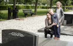 Young family visiting graveyard, standing at grave of deceased family