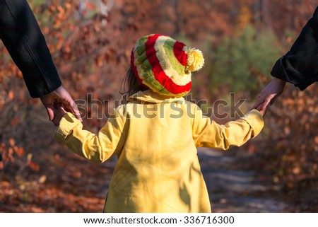 Young Family Walking on Park Alley Parents Holding Hands of Little Baby Daughter from both Sides Autumnal Colorful Forest on Background