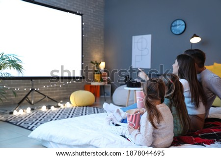 Young family watching movie at home Foto stock ©