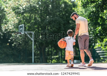 Young family with a ball on the basketball court
