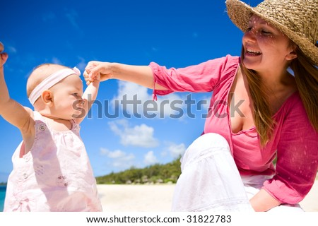 Young family with baby girl on white sand tropical beach