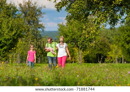 Young family with baby having a walk on a green meadow in the summer sun