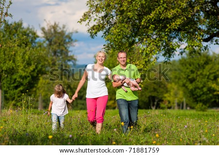 Young family with baby having a walk on a green meadow in the summer sun - stock photo