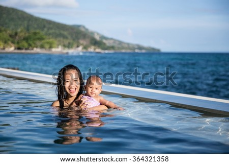 Young family with baby having fun in the swimming pool on summer day #364321358