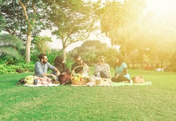 Young family with baby having picnic on green grass meadow in nature, cheerful concept, Arabic family