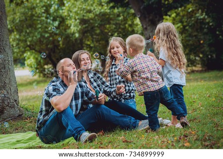 Young family with cheerful children in the park. Bubble blower #734899999