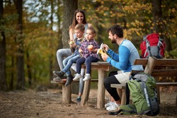 Young family with children having fruit snack on outing