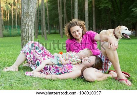Young Family with dog relaxing In Park/Happy family with dog//happy together