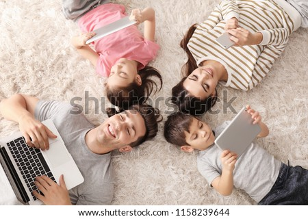 Young family with gadgets at home, top view