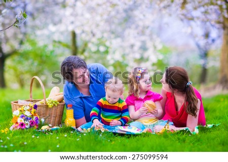 Young family with kids having picnic outdoors. Parents with two children relax in blooming summer garden. Mother, father, little girl and baby boy eat sandwich and fruit, drink juice for healthy lunch