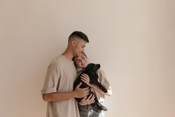 Young family with little black dog against light background. Cute young boy in beige loungewear hugging pretty lady holding puppy indoor