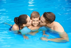 Young family with little son in swimming pool on sunny day