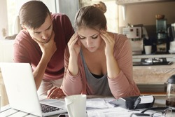Young family with many debts facing financial stress. Unemployed male looking pensive standing next to his depressed wife with headache who is calculating expenses, trying to make both ends meet