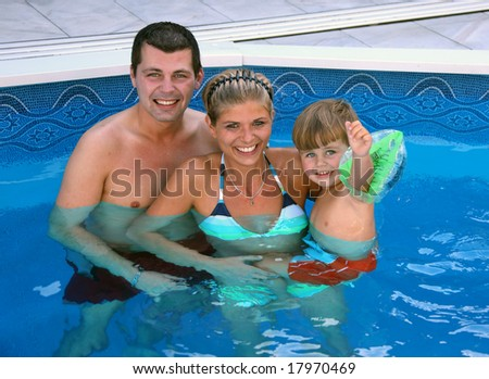Young family with one child in the pool