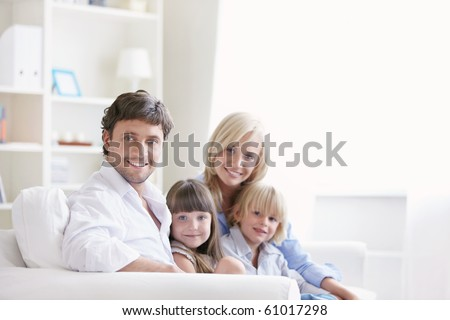 Young family with two children on a white sofa at home