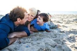 Young family with two small children lying down outdoors on beach.