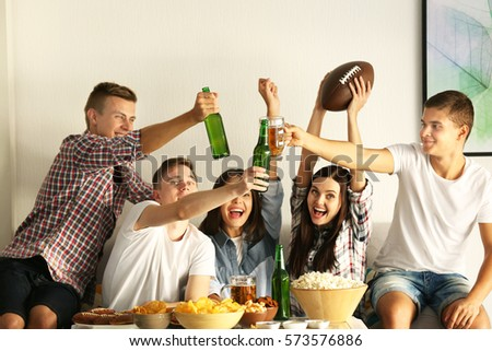 Young fans watching rugby match on TV with beer and snacks #573576886