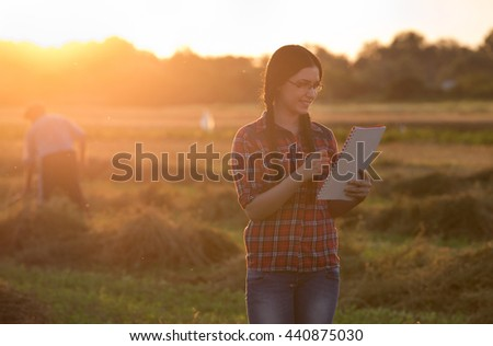 Young farmer girl writing notes on field in sunset while old peasant working with hay fork in background