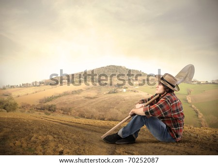 Young farmer sitting on a hill