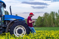 Young farmer using tablet in front of tractor in field. Smart and modern farm concept