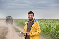 Young farmer with beard holding tablet in front of tractor in field. Seasonal agricultural works