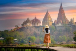 young farmer woman walks on wooden bridge terrace of rice to the temple at morning sunrise with scenerry view of buddhist temple pagoda in background