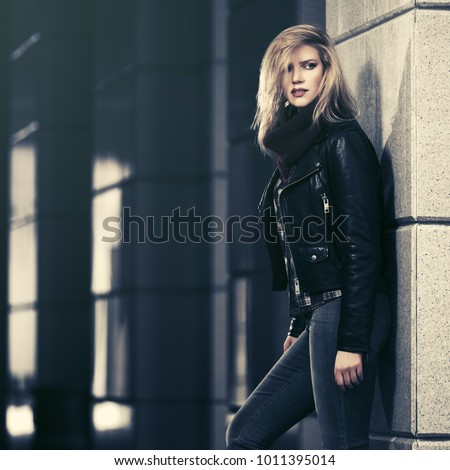 Young fashion blond woman walking on city street Stylish female model in black leather jacket and dark blue jeans