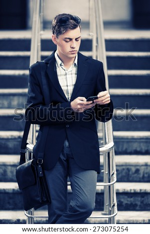 Young fashion business man looking at mobile phone