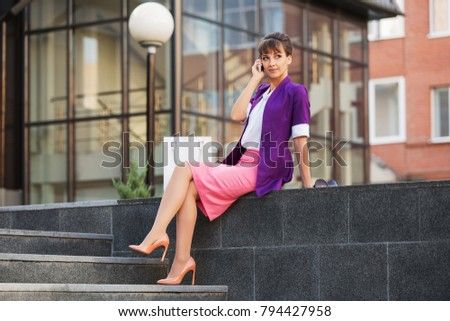 Young fashion business woman calling on cell phone at office building Stylish female model in purple blazer and pink pencil skirt