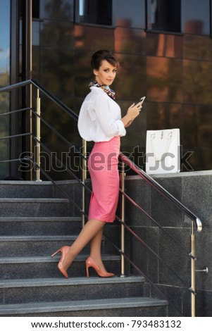 Young fashion business woman using tablet computer at office building Stylish female model in white blouse and pink pencil skirt