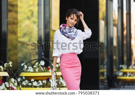 Young fashion business woman with handbag walking in city street Stylish female model in white blouse and pink pencil skirt