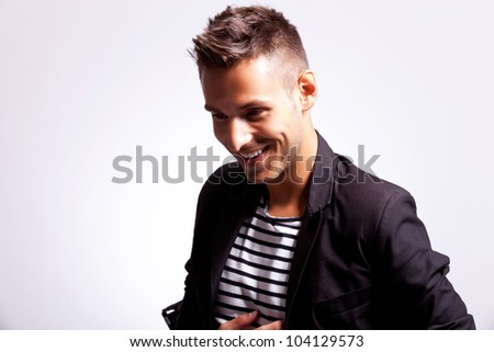 young fashion casual man laughing over grey background