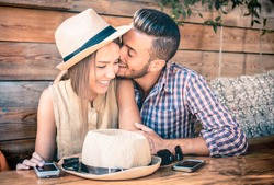 Young fashion couple of lovers at beginning of love story - Handsome man whispers kisses in pretty woman ear - Relationship concept with boyfriend and girlfriend together - Warm retro filter