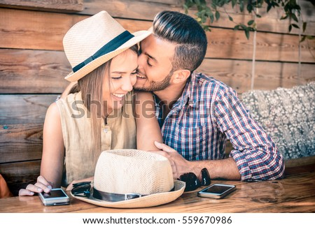 Young fashion couple of lovers at beginning of love story - Handsome man whispers sexy kisses in pretty woman ear - Relationship concept with boyfriend and girlfriend together - Warm retro filter