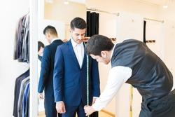 Young fashion designer taking measurement of man wearing elegant suit in tailor shop