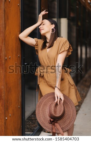 Young fashion girl dressed in a summer dress with a wicker wide hat walks and poses in the old city. Street fashion portrait of young beautiful woman walking in the city