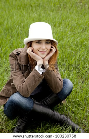 Young fashion girl in white hat at green spring grass.