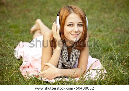 Young fashion girl with headphone lying at green grass at park.
