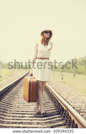 Young fashion girl with suitcase at railways. - stock photo