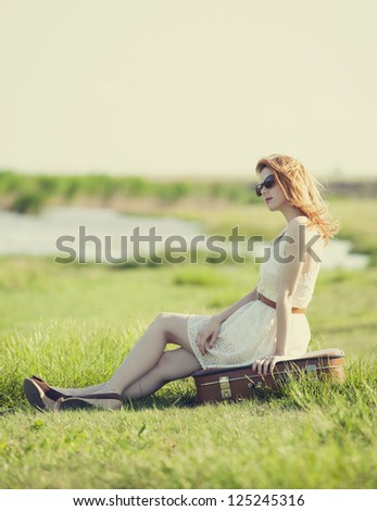 Young fashion girl with suitcase sitting at spring grass near lake.