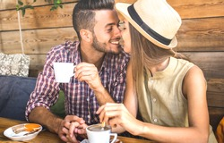 Young fashion lovers couple at beginning of love story - Handsome man kissing beautiful woman at coffee shop bar - Relationship concept with happy boyfriend and girlfriend together - Warm retro filter